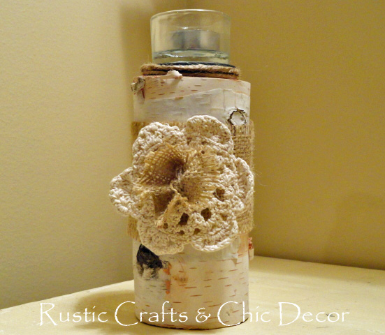 Birch candle holder wrapped in burlap and embellished with a doily and burlap flower.