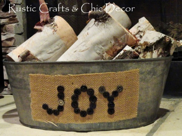 Tin bucket with a button and burlap label filled with birch logs.