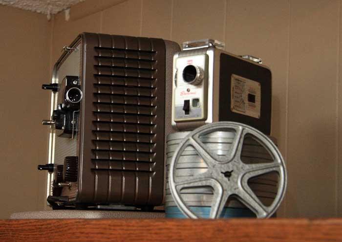 old film reel displayed with vintage cameras