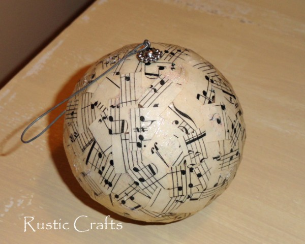 Christmas ornament ball covered with song sheet pieces