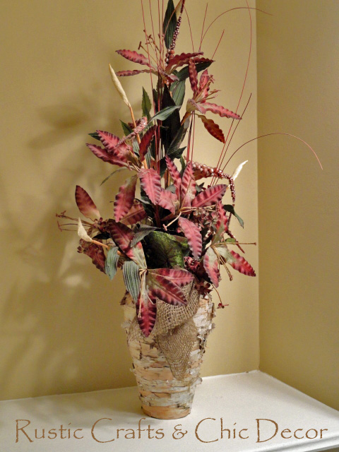 Rustic birch vase with a burlap garland tie and burgundy flowers.