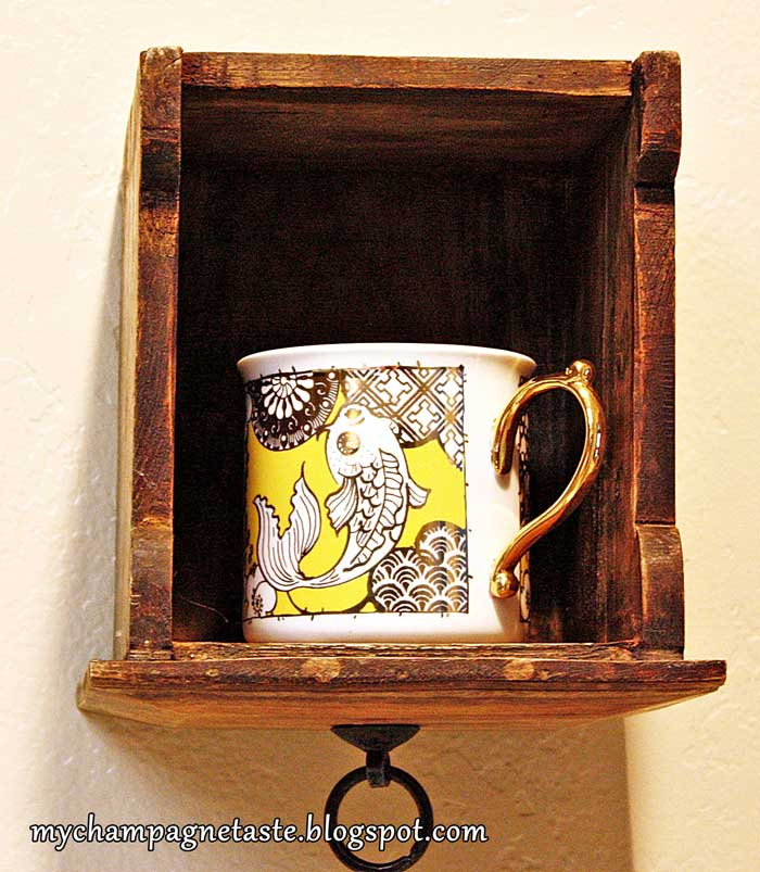 repurposed drawer on wall for mug display